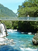 Walker crossing the Hollyford River